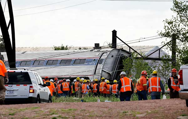 <div class='meta'><div class='origin-logo' data-origin='AP'></div><span class='caption-text' data-credit='AP Photo/Mel Evans'>Emergency personnel gather near the scene of a deadly train derailment, Wednesday, May 13, 2015, in Philadelphia.</span></div>