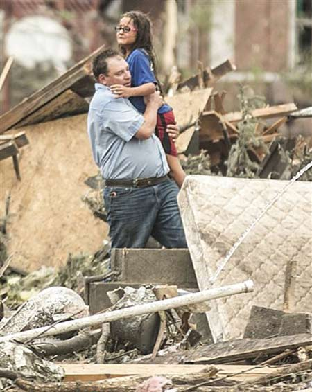 A man holds a girl after she was pulled from the basement of her destroyed home in Pilger, Neb., Monday, June 16, 2014. (AP Photo/Mark 'Storm' Farnik) <span class=meta></span>