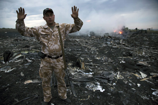 A man gestures at a crash site of a passenger plane near the village of Grabovo, Ukraine, Thursday, July 17, 2014. <span class=meta>AP Photo/Dmitry Lovetsky</span>