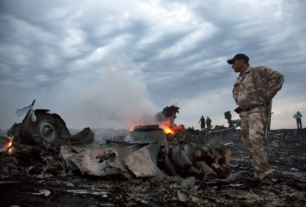 People walk amongst the debris, at the crash site of a passenger plane near the village of Grabovo, Ukraine, Thursday, July 17, 2014. <span class=meta>AP Photo/Dmitry Lovetsky</span>