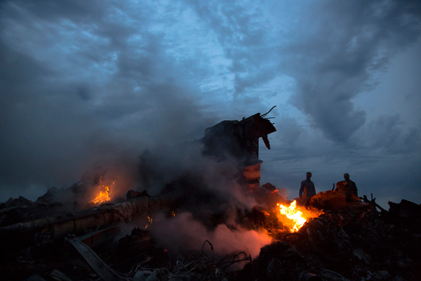 People walk amongst the debris at the crash site of a passenger plane near the village of Grabovo, Ukraine, Thursday, July 17, 2014. <span class=meta>AP Photo/Dmitry Lovetsky</span>