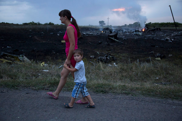 A woman with a child walks past the crash site of a passenger plane near the village of Grabovo, Ukraine, Thursday, July 17, 2014. <span class=meta>AP Photo/Dmitry Lovetsky</span>