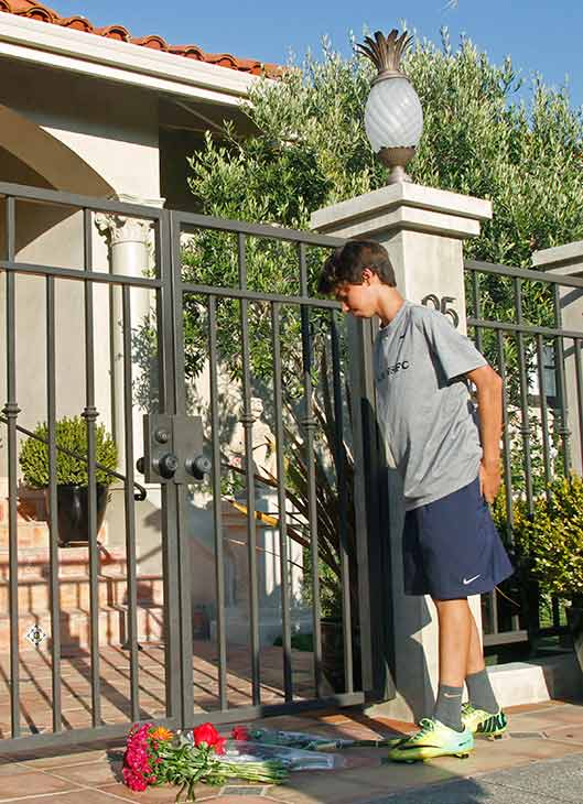 A boy stands by flowers at the home of Robin Williams, Monday, Aug. 11, 2014, in Tiburon, Calif. (AP Photo/George Nikitin) <span class=meta></span>
