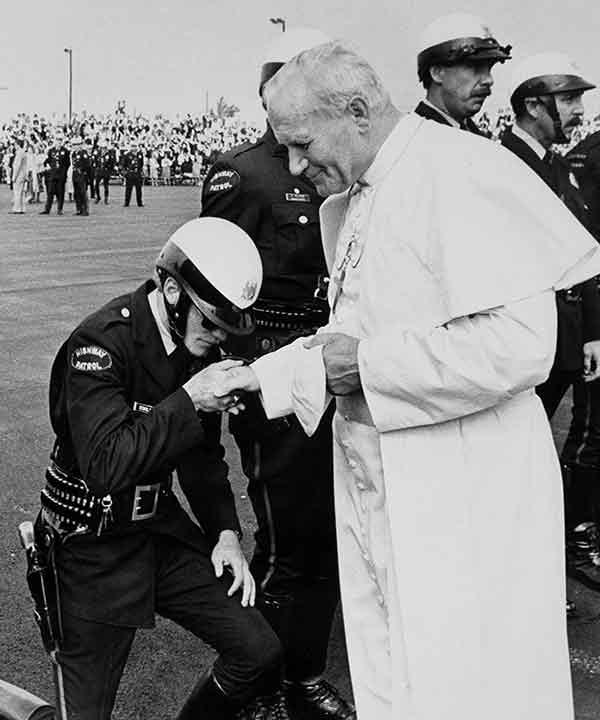 <div class='meta'><div class='origin-logo' data-origin='AP'></div><span class='caption-text' data-credit=''>A Pennsylvania Highway patrolman kisses the hand of Pope John Paul II as he prepares to leave for Des Moines, Iowa, from the airport in Philadelphia,</span></div>