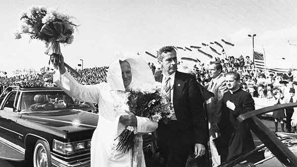 <div class='meta'><div class='origin-logo' data-origin='AP'></div><span class='caption-text' data-credit=''>Pope John Paul II escorted by a Secret Service agent, waves a bouquet of flowers and holds another after arriving at Philadelphia International Airport, Oct. 3, 1979.</span></div>