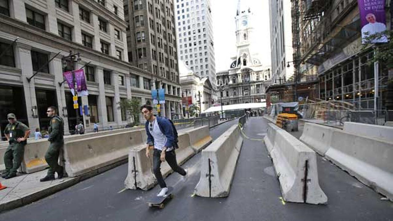 A man on a skateboard rides through a security checkpoint on Broad Street with City Hall in the background in Philadelphia on Friday, Sept. 25, 2015.AP Photo/Alex Brandon