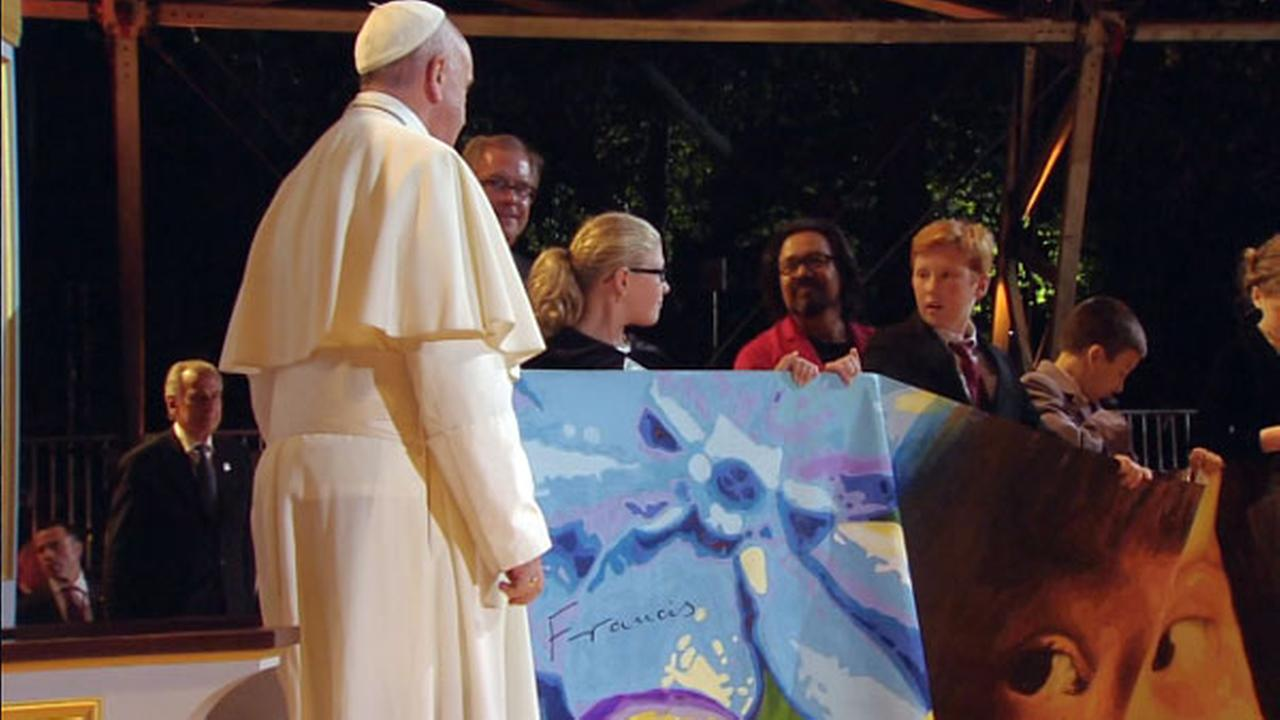 Pope Francis signs a commemorative mural from the World Meeting of Families at the Festival of Families in Philadelphia.