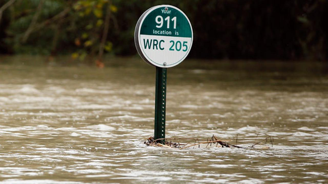 A 911 location marker sits on a flooded bike and walking path by White Rock Lake after heavy rain fall soaked the region Friday, Oct. 23, 2015, in Dallas.