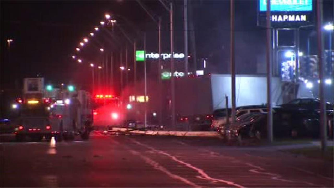 Rescue crews are working to free a truck driver after his big rig crashed into a pole in the parking lot of a car dealership in Southwest Philadelphia.