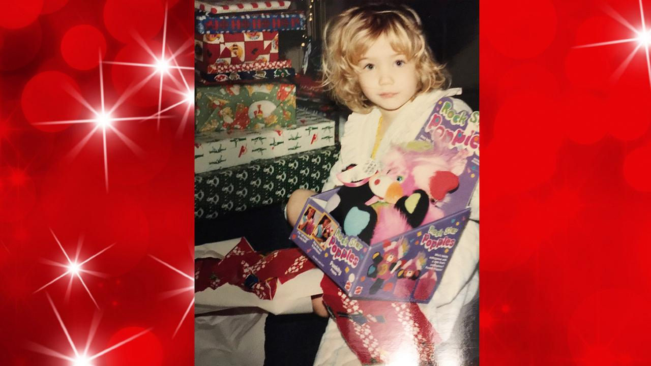 4-year-old Trish Hartman unwraps a present from Santa on Christmas morning - bed head and all!