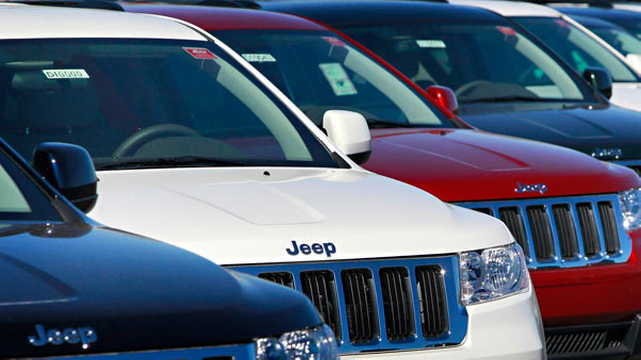 A row of 2011 Jeep Grand Cherokees are shown Tuesday, Nov. 30, 2010 at a dealership in Mesa, Ariz.