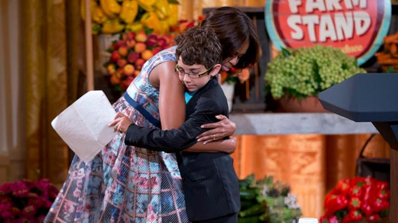 First lady Michelle Obama, left, hugs last years winner from Delaware, Braeden Mannering, during the Kids State Dinner in the East Room of the White House in Washington, Friday,