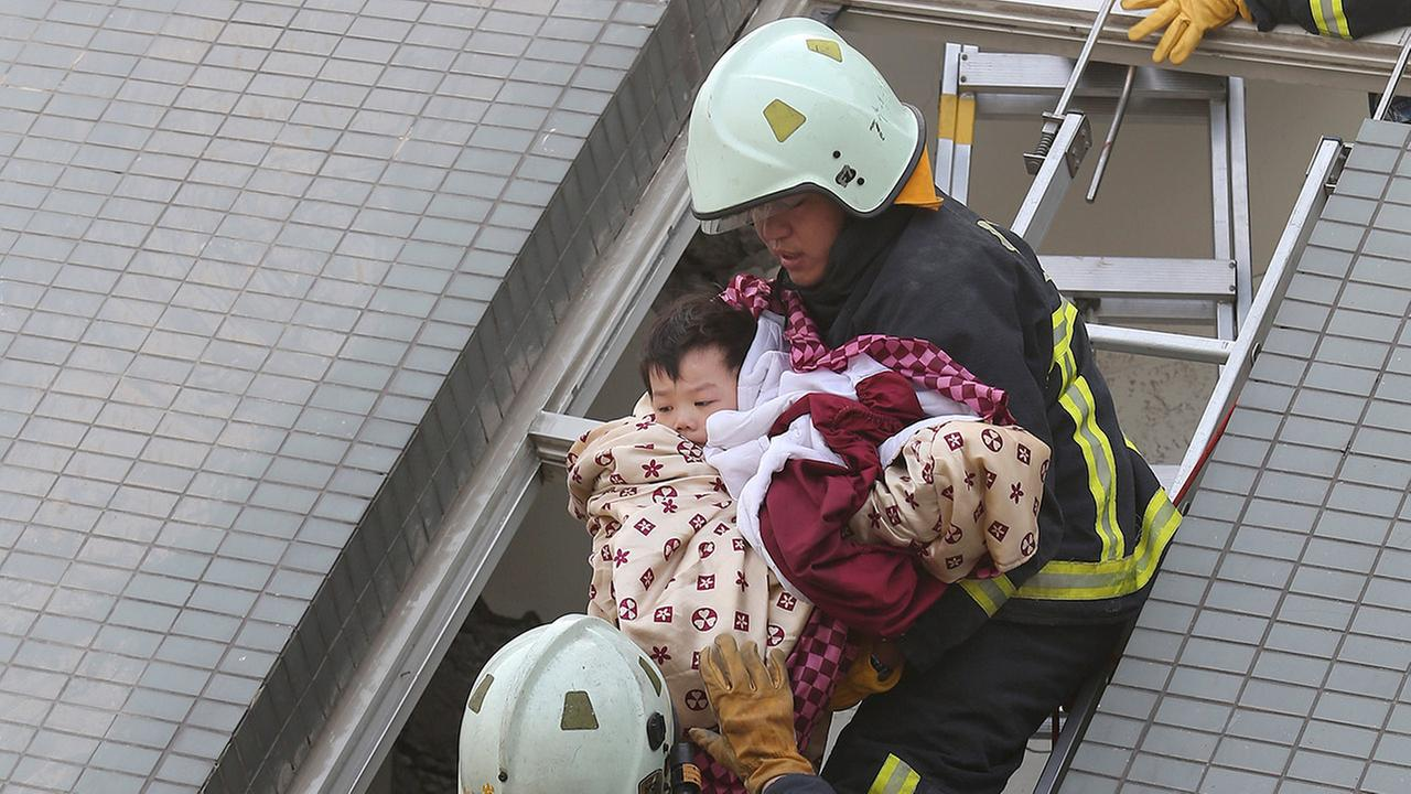 A child is rescued from a toppled building after a 6.4-magnitude earthquake in Tainan, Taiwan, Saturday, Feb. 6, 2016.