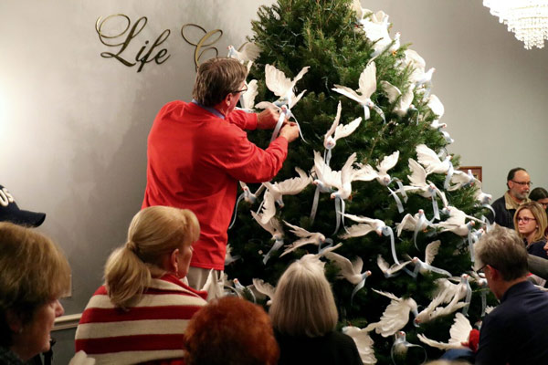 """<div class=""""meta image-caption""""><div class=""""origin-logo origin-image none""""><span>none</span></div><span class=""""caption-text"""">Life Celebration by Givnish staff helps Memorial Tree Service attendees place their white dove on the tree in honor of their loved ones</span></div>"""