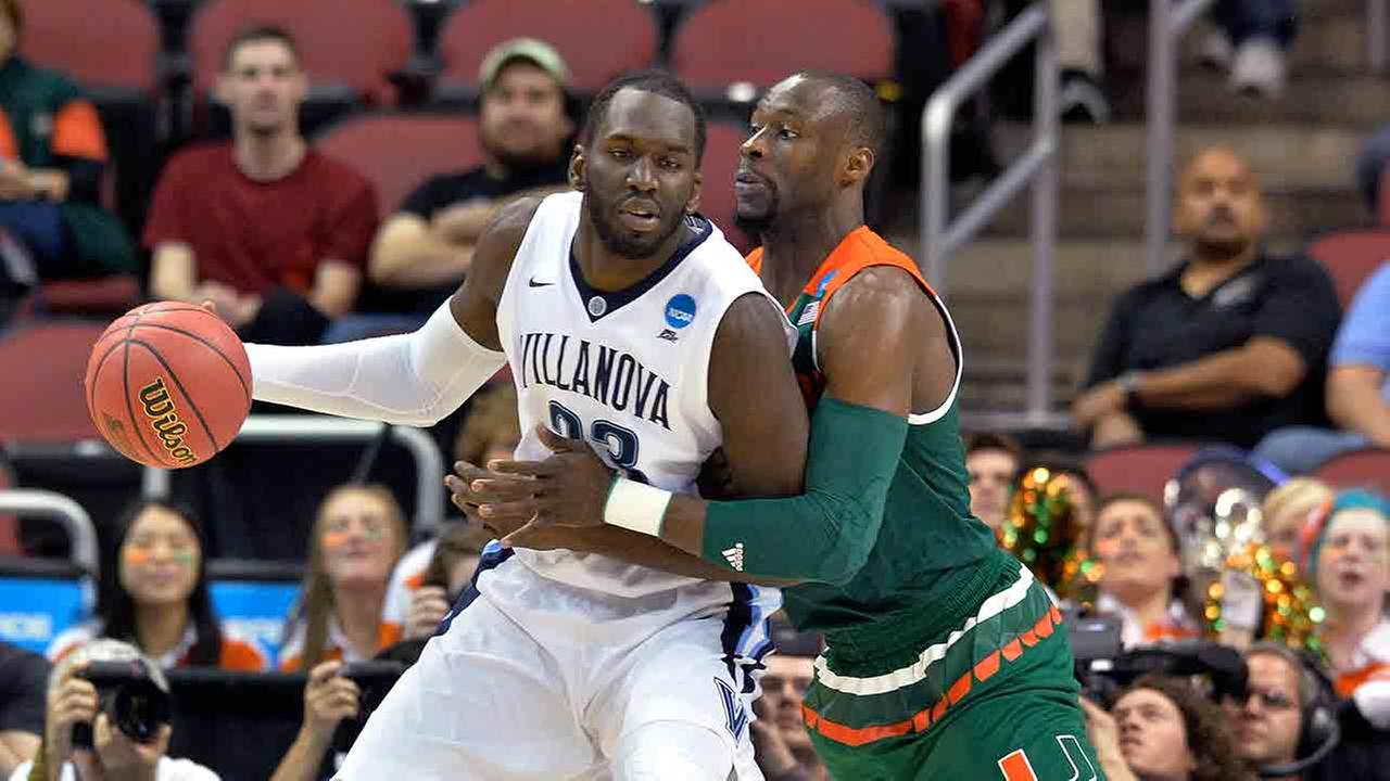 Villanova forward Daniel Ochefu is guarded by Miami center Tonye Jekiri during the first half of an NCAA college basketball game in the regional semifinals of the NCAA Tournament.