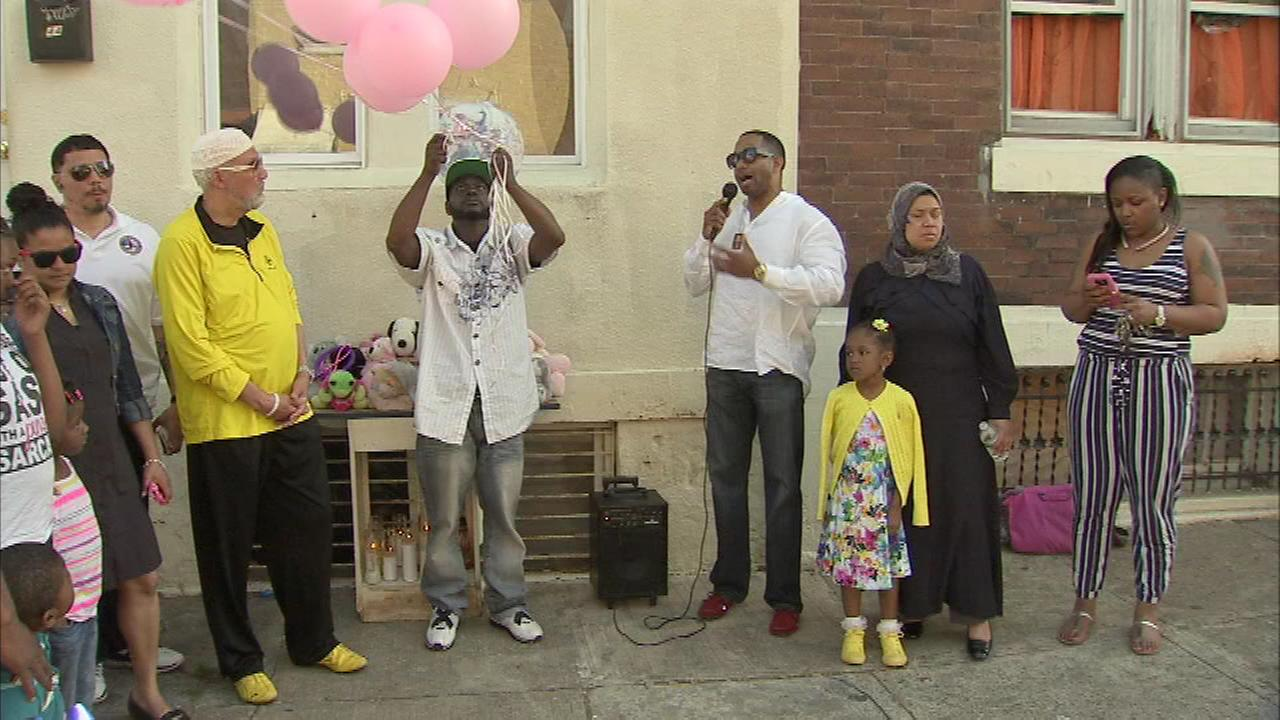 Neighbors hold a vigil for a 4-year-old girl who was shot and killed by her father while he allegedly played with a gun.