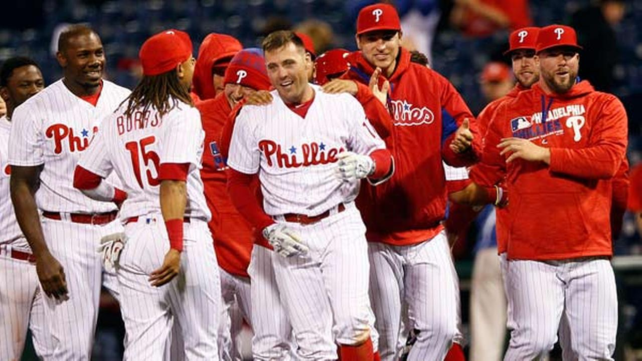Philadelphia Phillies Peter Bourjos, center, is surrounded by teammates after Freddy Galvis scored on Bourjos single in the 11th inning.