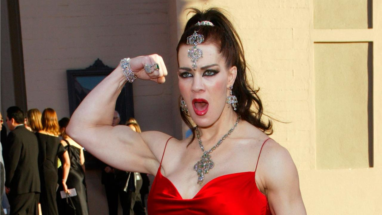 In this Nov. 16, 2003 file photo, Joanie Laurer, former pro wrestler known as Chyna, flexes her bicep as she arrives at the 31st annual American Music Awards