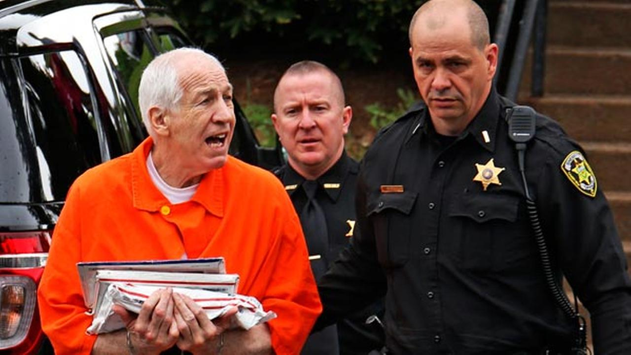 Former Penn State University assistant football coach Jerry Sandusky, left, talks with reporters as he arrives at the Centre County Courthouse.