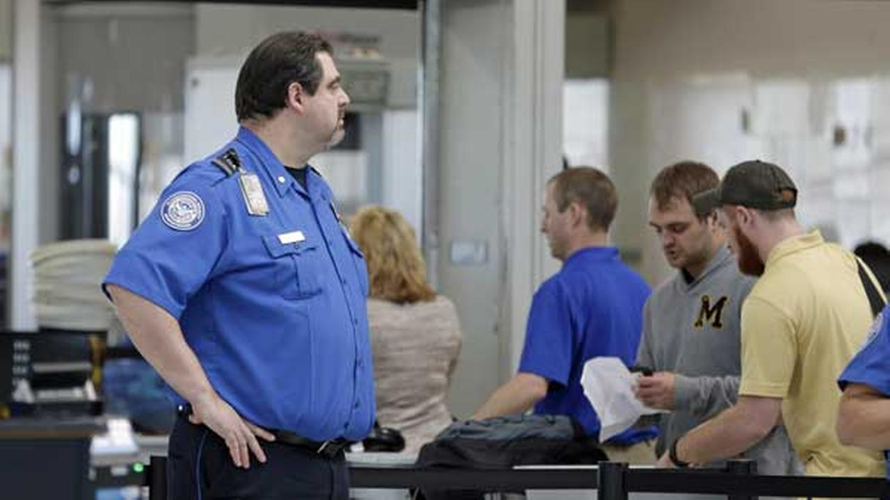 A Transportation Security Administration inspector watches as travelers move through a security checkpoint at Lambert-St. Louis International Airport Tuesday, April 12, 2016.