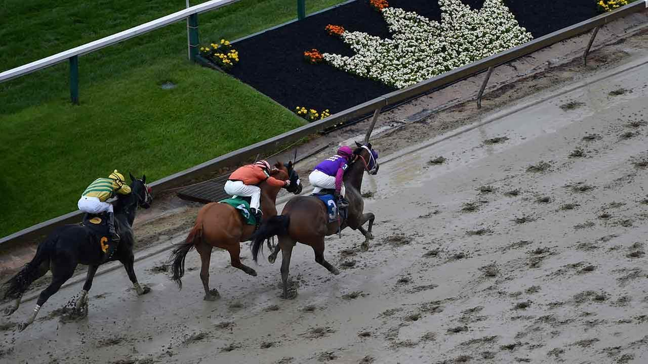 Homeboykris (3), ridden by Horacio Karamanos, head to the finish to win the first race of the day on a muddy track ahead of the 141st Preakness Stakes horse race.