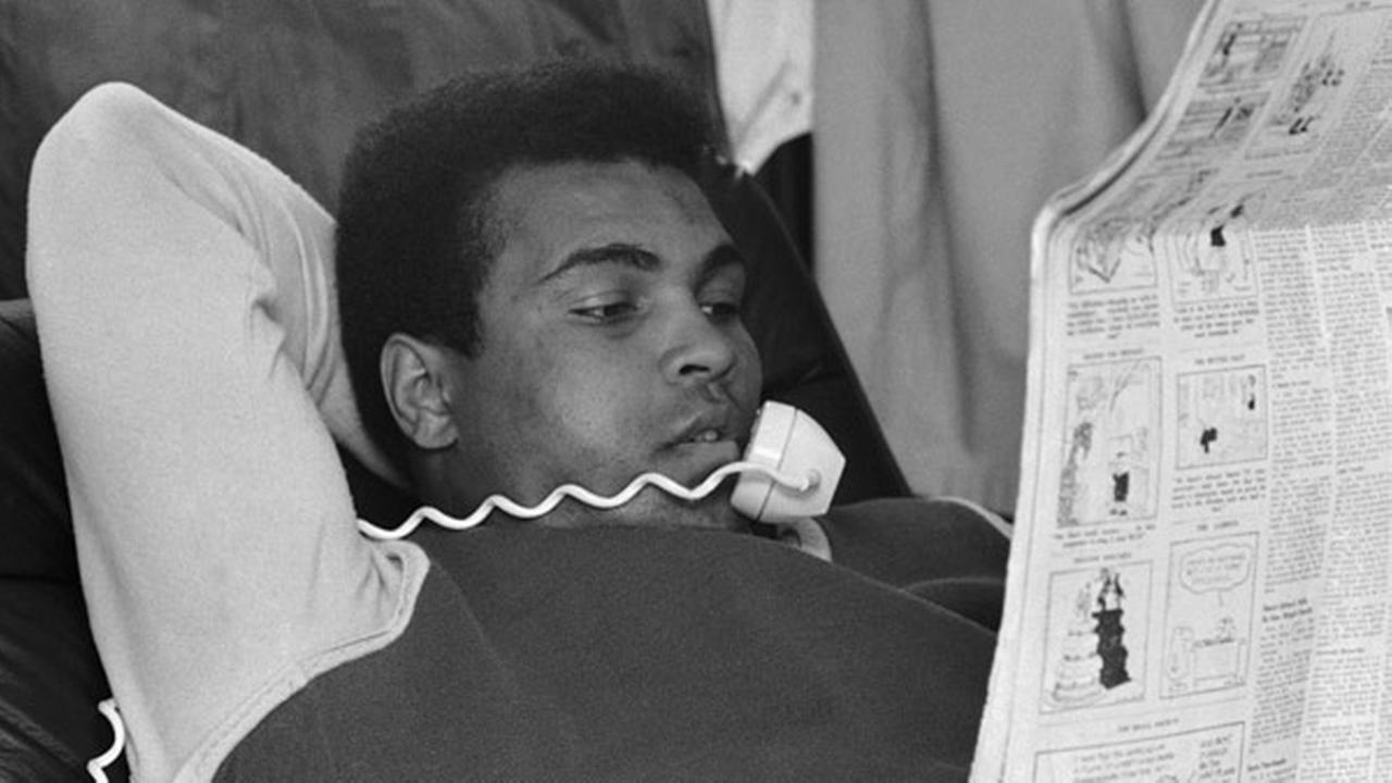 Muhammad Ali has phone to his ear and looks over a newspaper in his plush new home at Cherry Hill, New Jersey on Wednesday, March 10, 1971.AP Photo