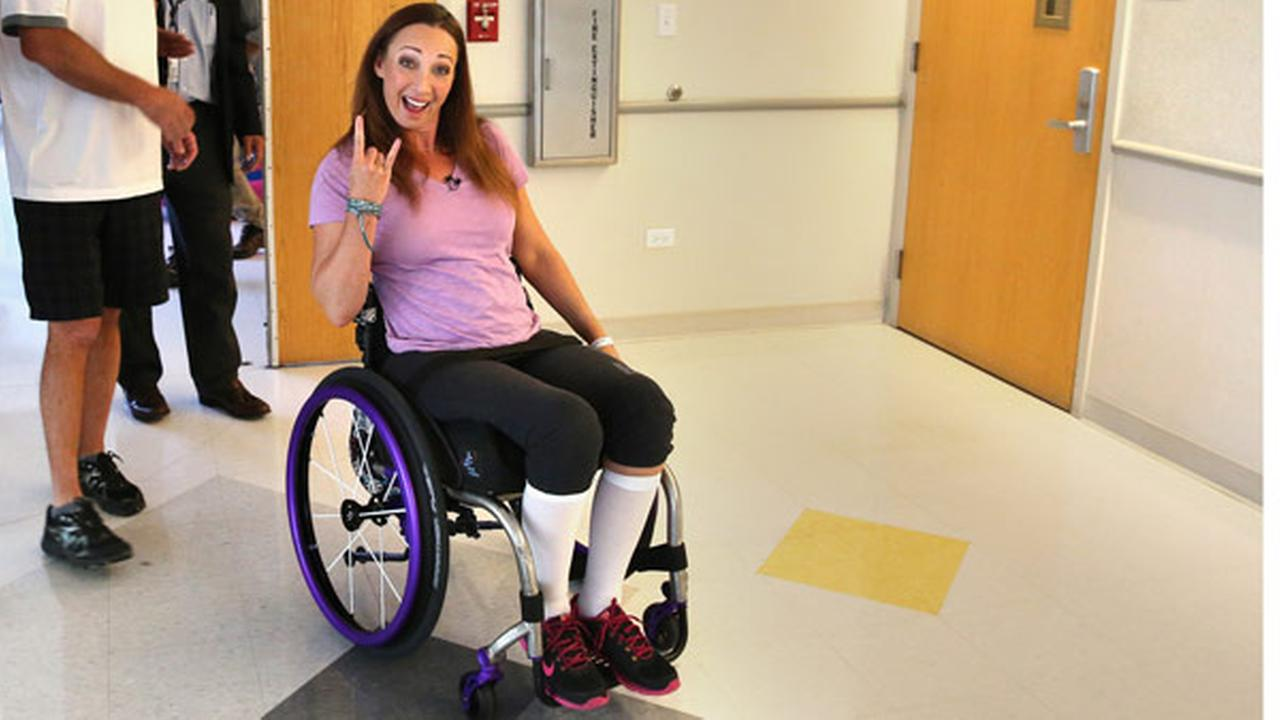 FILE - In this Aug. 14, 2014, file photo, Amy Van Dyken-Rouen gestures as she leaves Craig Hospital with her husband, Tom Rouen, left, in Englewood, Colo.