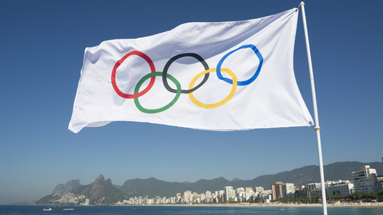 RIO DE JANEIRO, BRAZIL - FEBRUARY 12, 2015: An Olympic flag flies above the city skyline at Ipanema Beach with a view of Two Brothers Mountain.