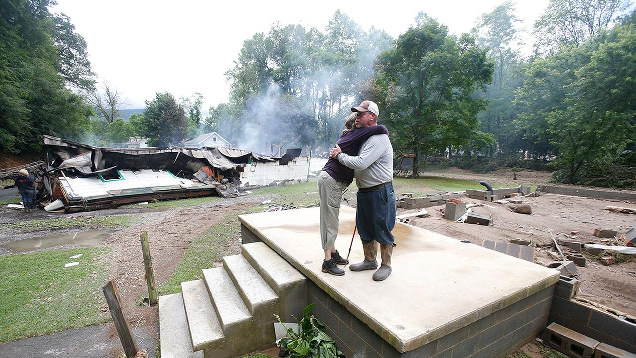Jimmy Scott gets a hug from Anna May Watson, left, as they clean up from severe flooding in White Sulphur Springs, W. Va., Friday, June 24, 2016.