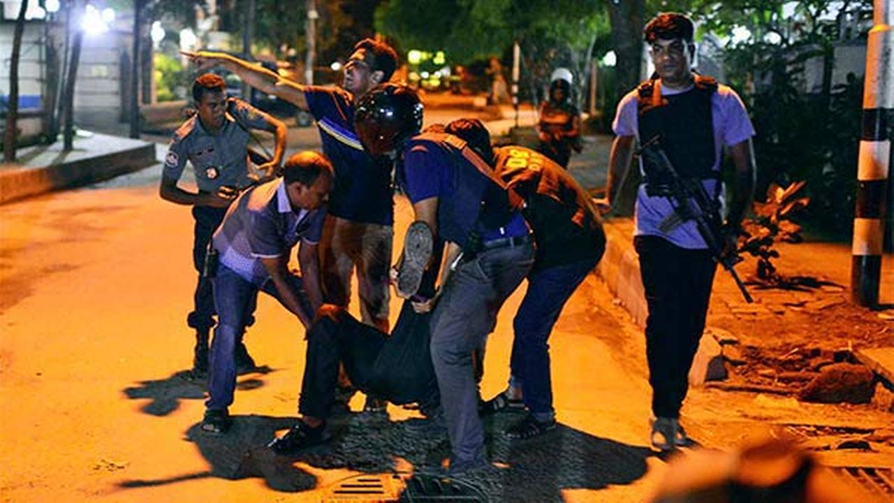 People help an unidentified injured person after a group of gunmen attacked a restaurant popular with foreigners in a diplomatic zone of the Bangladeshi capital Dhaka, Bangladesh.
