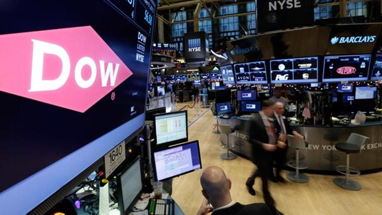 FILE - In this Dec. 9, 2015 file photo, the company names of Dow, left, and Dupont, right, appear above their trading posts on the floor of the New York Stock Exchange.