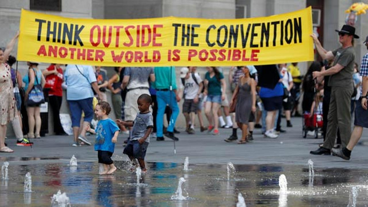 Demonstrators carry a sign around Dillworth Park as two youngsters play in the fountain on Sunday, July 24, 2016, in Philadelphia. The Democratic National Convention starts Monday.