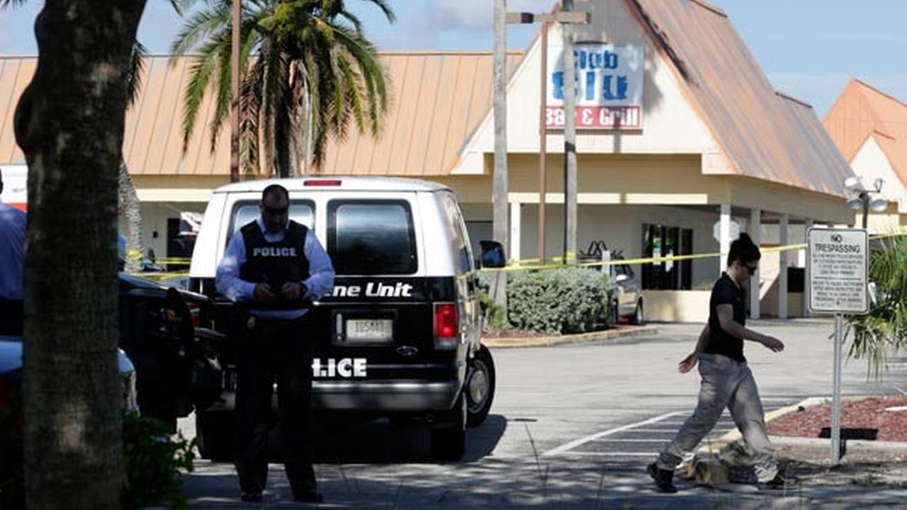 Officials investigate the scene of a deadly shooting outside the Club Blu nightclub, Monday, July 25, 2016, in Fort Myers, Fla. Gunfire erupted at the nightclub.