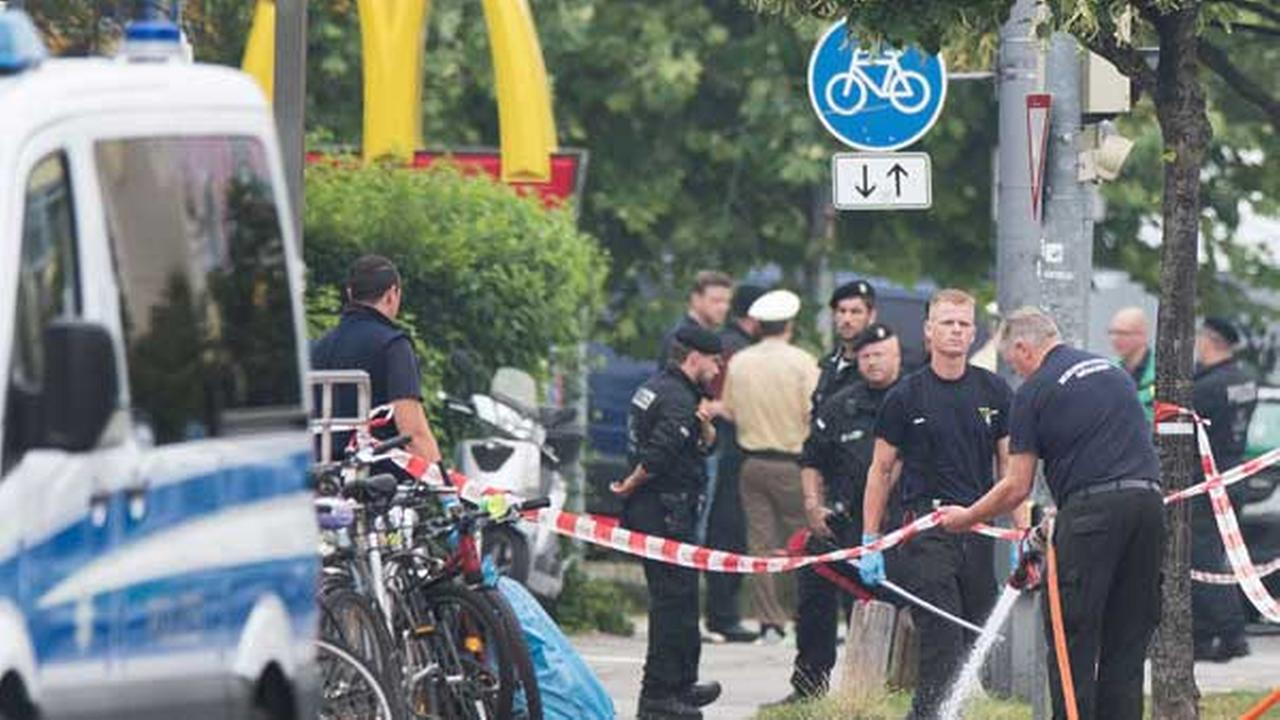 Police stand at a the crime scene where a shooting took place in front of a fast food restaurant leaving nine people dead the day before on Saturday, July 23, 2016 in Munich.