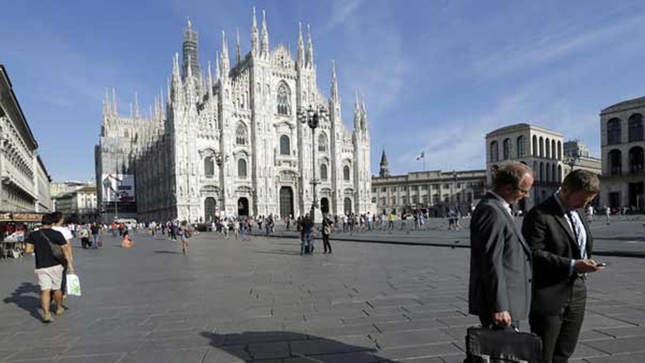 FILE - Two men walk in front of the Duomo gothic cathedral, in Milan, Italy.