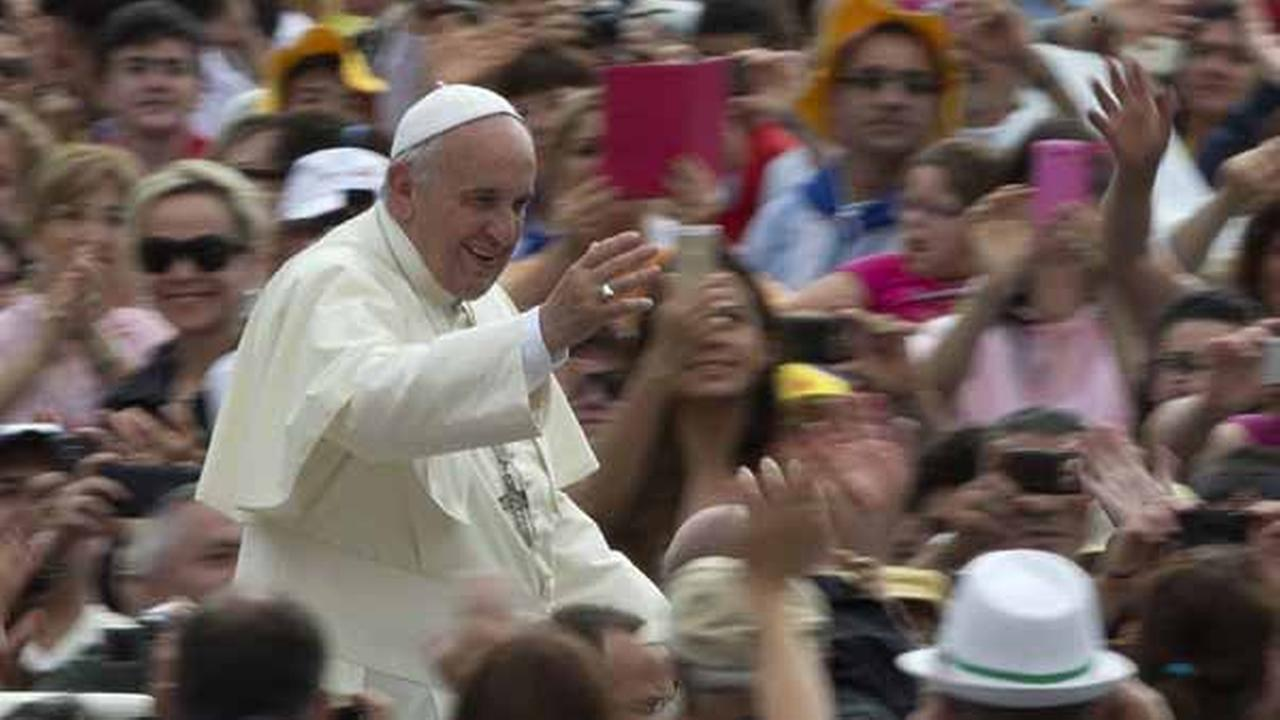 Pope Francis waves as he is driven through the crowd during his weekly general audience in St. Peters Square at the Vatican, Wednesday, June 25, 2014.