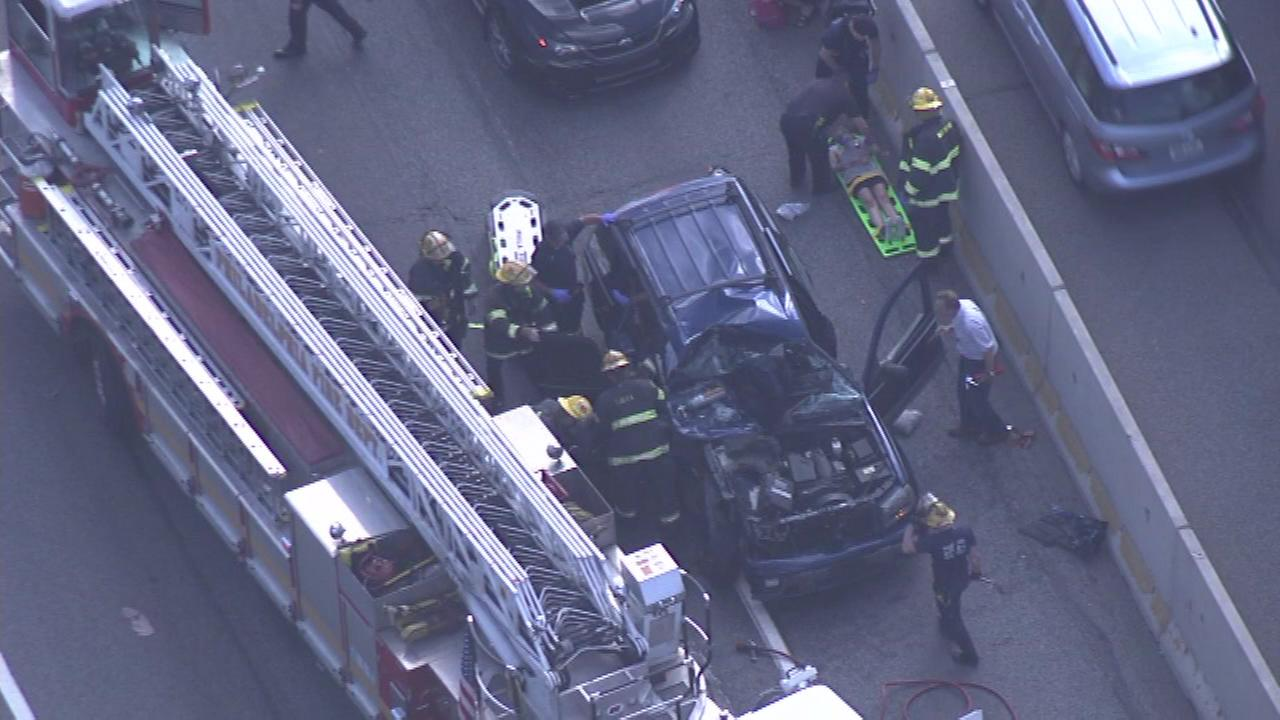 August 3, 2016: Video from Chopper 6 HD showed more than a dozen firefighters surrounding a blue vehicle with extensive damage to the hood and windshield.