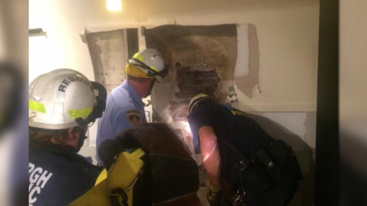 Rescuers had to cut a hole through a buildings wall to rescue the trapped man.