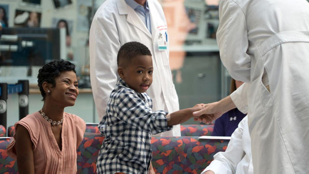 Zion Harvey, center, who received a double hand transplant in July 2015, shakes hands with a health care worker as his mother Pattie Ray, left, smiles.