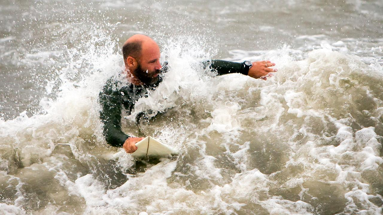 A surfer looks for a wave from the surge of Hurricane Hermine, Friday, Sept. 2, 2016, off the coast of Tybee Island, Ga.