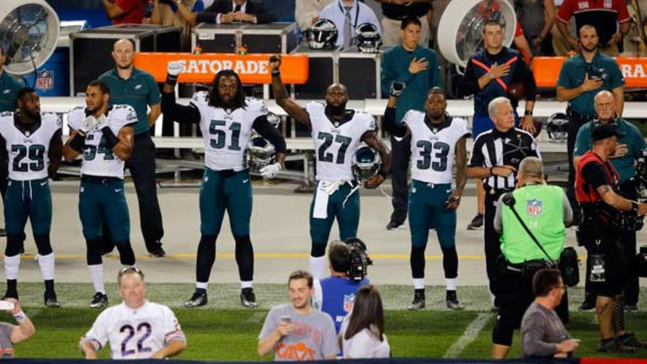 Malcolm Jenkins other Eagles hold up fists during anthem