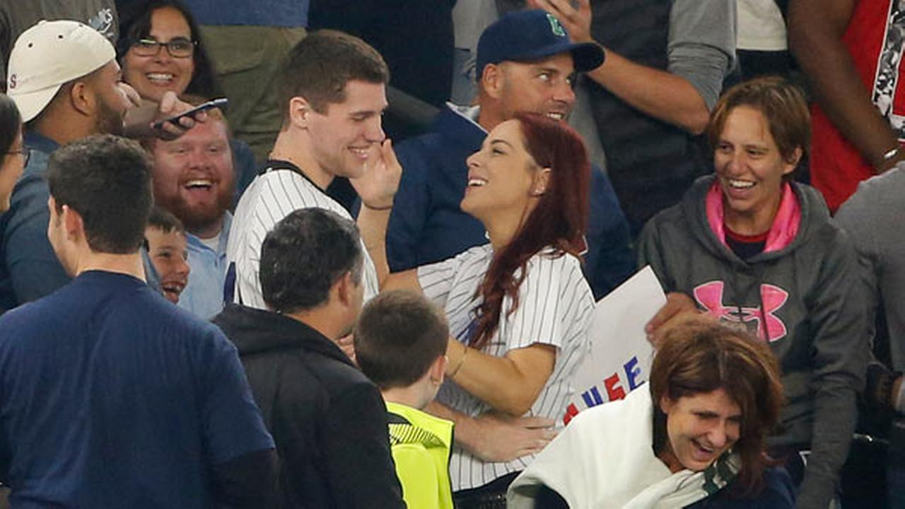 Fans laugh as Andrew Fox and Heather Terwilliger smile during a baseball game between the New York Yankees and the Boston Red Sox at Yankee Stadium in New York.