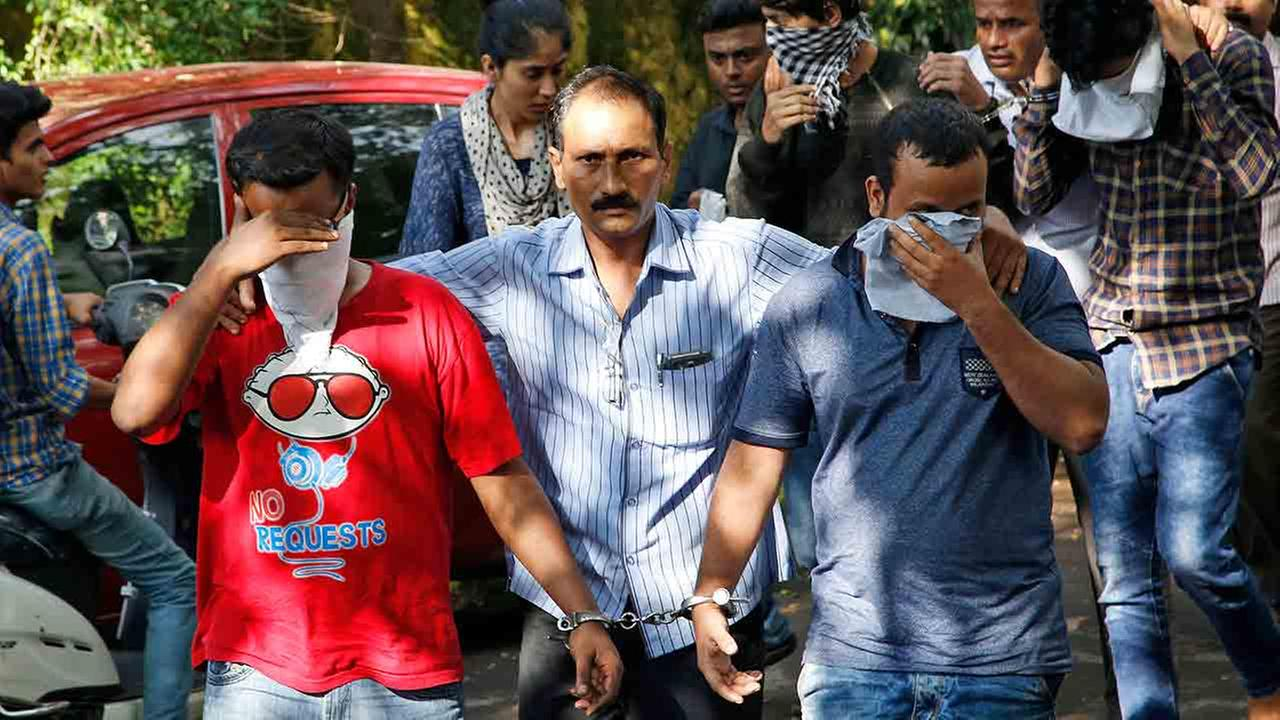A police official, center, escorts two men outside the court in Thane, outskirts of Mumbai, India, Thursday, Oct. 6, 2016.