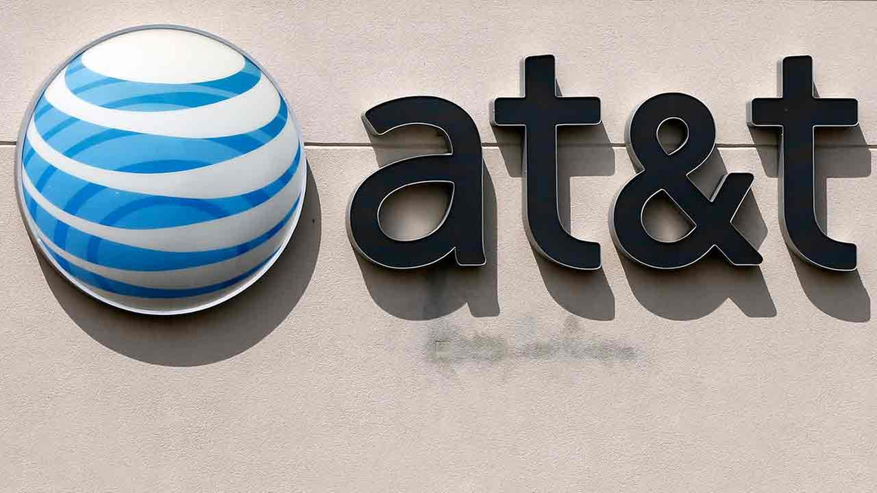 FILE - This May 14, 2014 file photo shows an AT&T logo on a store in Dedham, Mass.