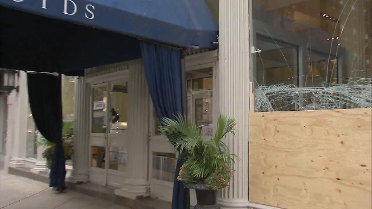Crews work to repair a damaged window from a break-in at Boyds in Center City Philadelphia.