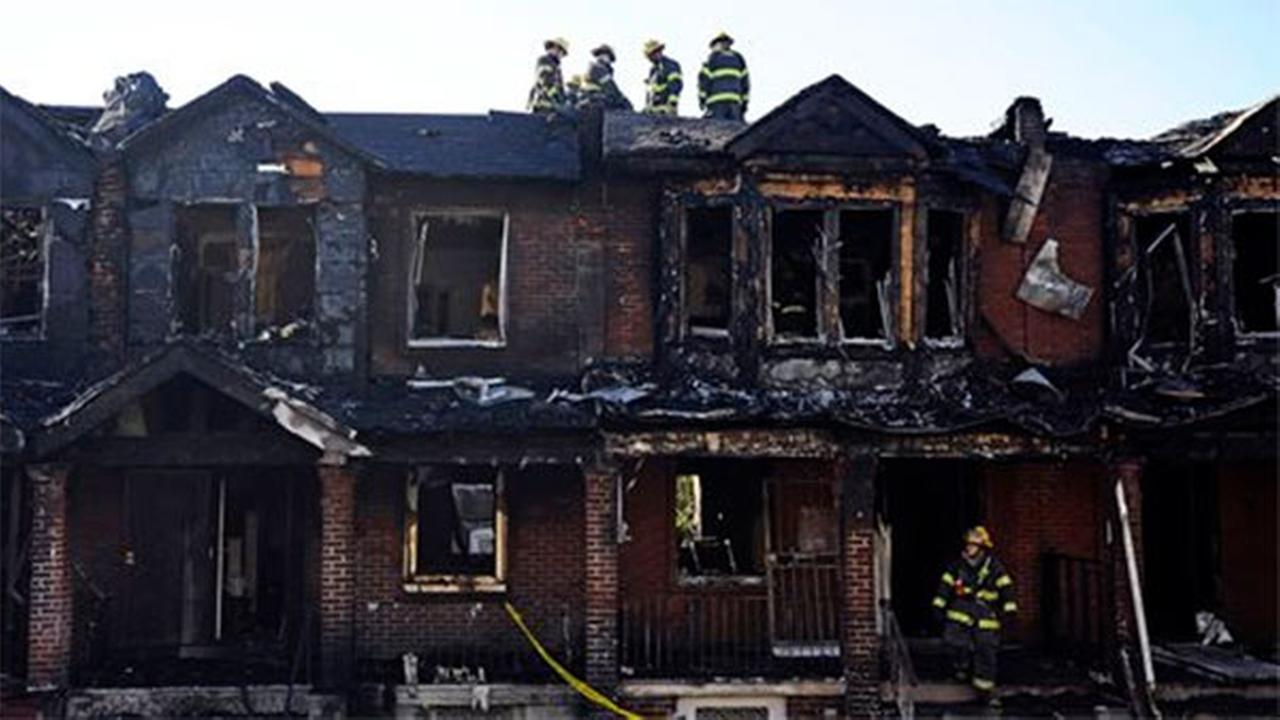 Philadelphia firefighters work on burned row homes on Saturday, July 5, 2014, in Philadelphia. (AP Photo/Michael Perez)