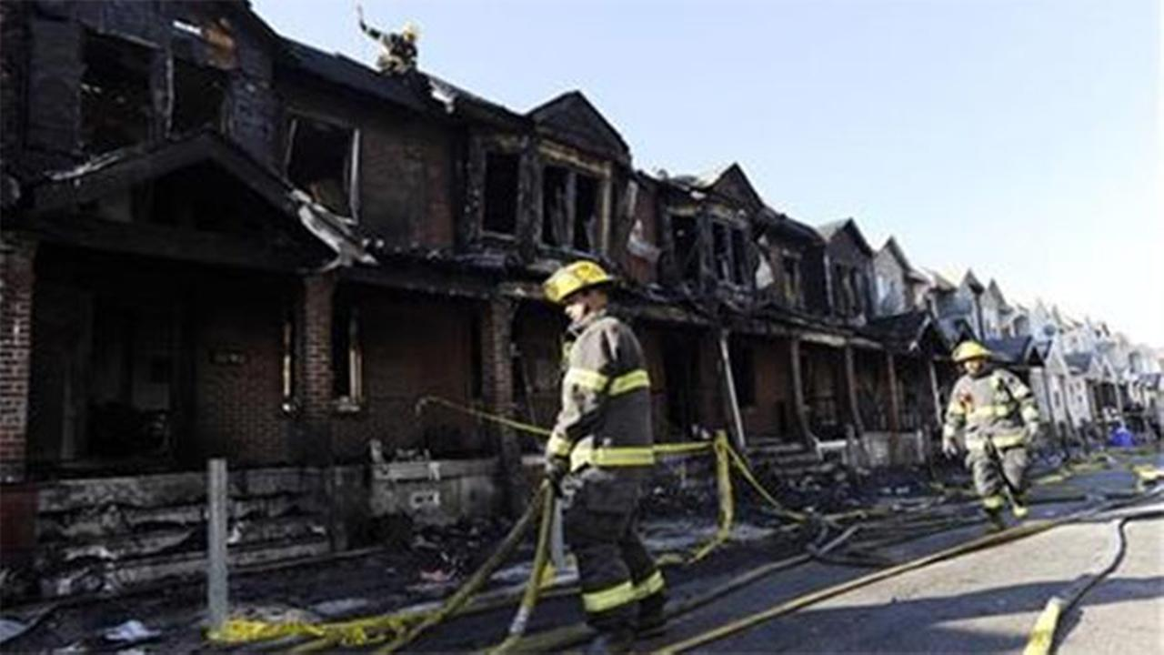 Philadelphia firefighters working on burned row homes on Saturday, July 5, 2014, in Philadelphia. (AP Photo/Michael Perez)
