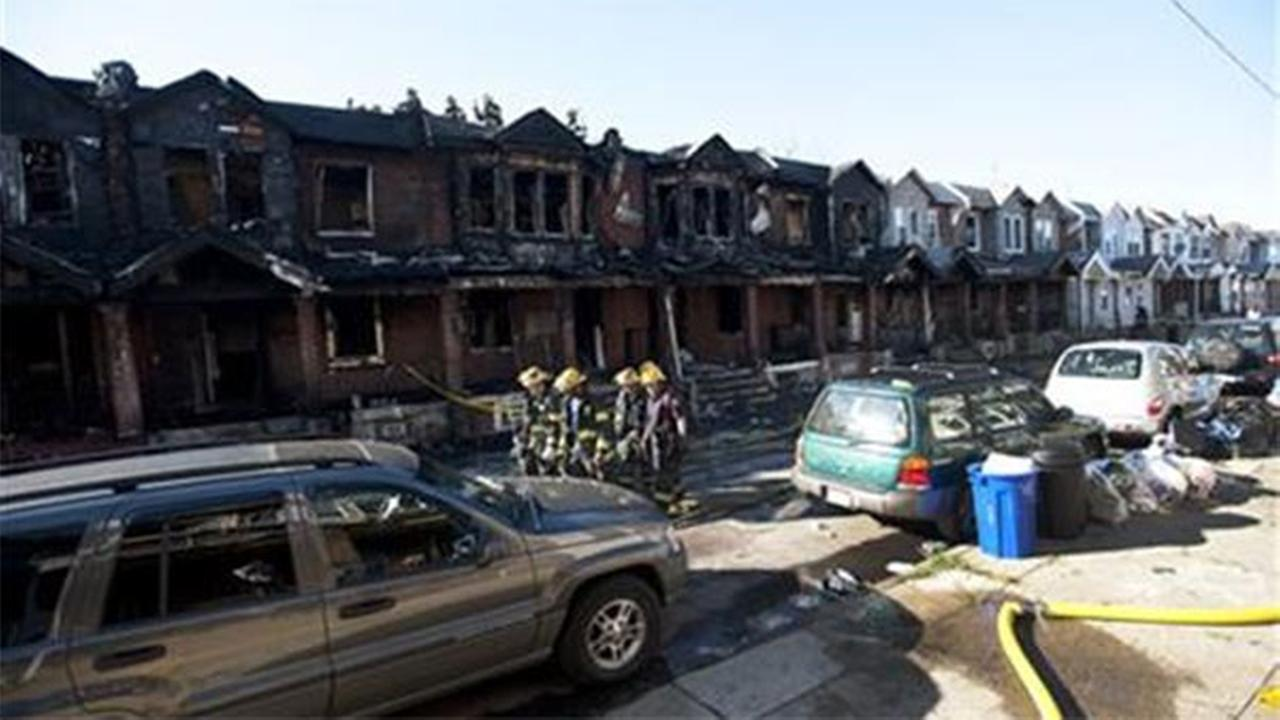 Philadelphia firefighters walk past burned row homes on Saturday, July 5, 2014, in Philadelphia after a fast-moving row house fire early Saturday left four children dead.(AP Photo/Michael Perez)