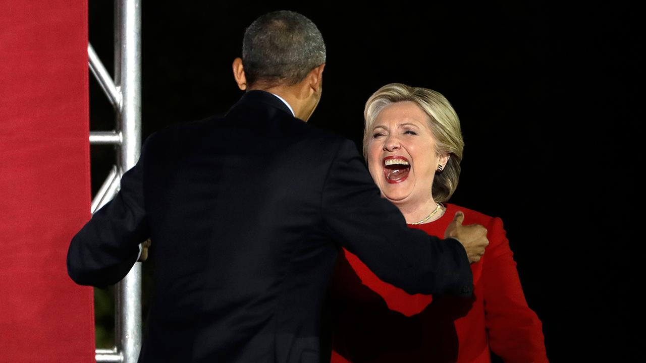 Democratic presidential candidate Hillary Clinton takes the stage during a campaign event at Independence Mall as she is greeted by President Barack Obama.