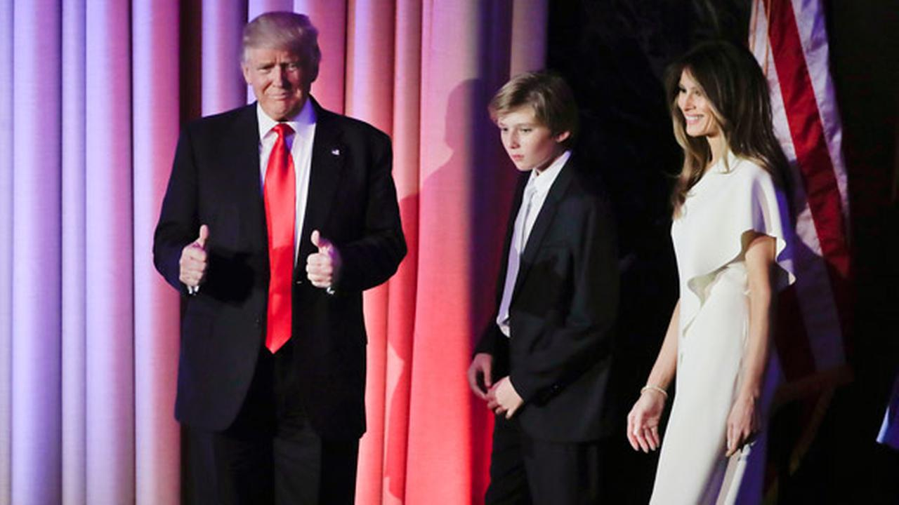 President elect Donald Trump motions to supporters as he and his son, Barron Trump, center, and wife, Melania Trump, walk on stage at an election night rally.
